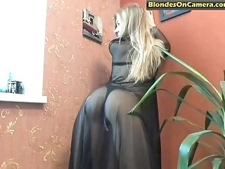 Blonde Woman In See Thru Sundress Taunts While Standing Next To A Window
